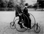 Smartly dressed couple seated on an 1886-model bicycle for two. The South Portico of the White House, Washington, D.C., in the background. (Courtesy of the National Archives)