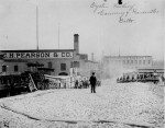 Man with a derby hat stands atop a mound of oyster shells outside the C. H. Pearson & Company oyster cannery, Baltimore. Workers bring wheel- barrows of shells from the factory to the heap. ca. 1890. (Courtesy of the National Archives)