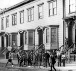 Children play ball in the street in front of typical housing with five rooms per family for 0 to 2 per month. San Francisco, ca. 1900. (Courtesy of the National Archives)