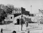 An Indian enclave in Albuquerque, N. Mex. Primitive shelters with modern city street behind. 1912. (Courtesy of the National Archives)