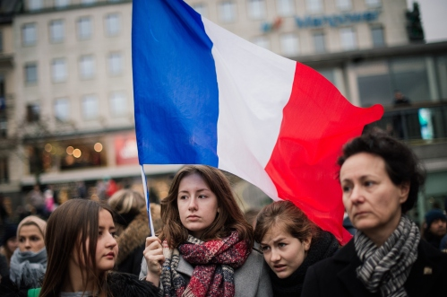 A woman holds a flag of France during a gathering in solidarity for France a day after deadly attacks in Paris on November 14, 2015 in Stockholm. Two Swedish citizens may be among the victims of the attacks that killed more than 120 people in Paris, the foreign ministry said. AFP PHOTO / JONATHAN NACKSTRAND        (Photo credit should read JONATHAN NACKSTRAND/AFP/Getty Images)